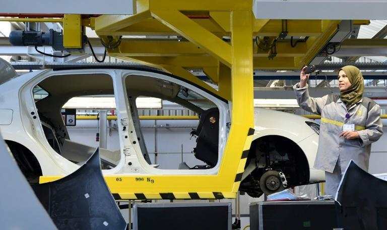 An employee of French carmaker Renault group takes a picture of a car in production at a plant, in the south of the Algerian city of Oran