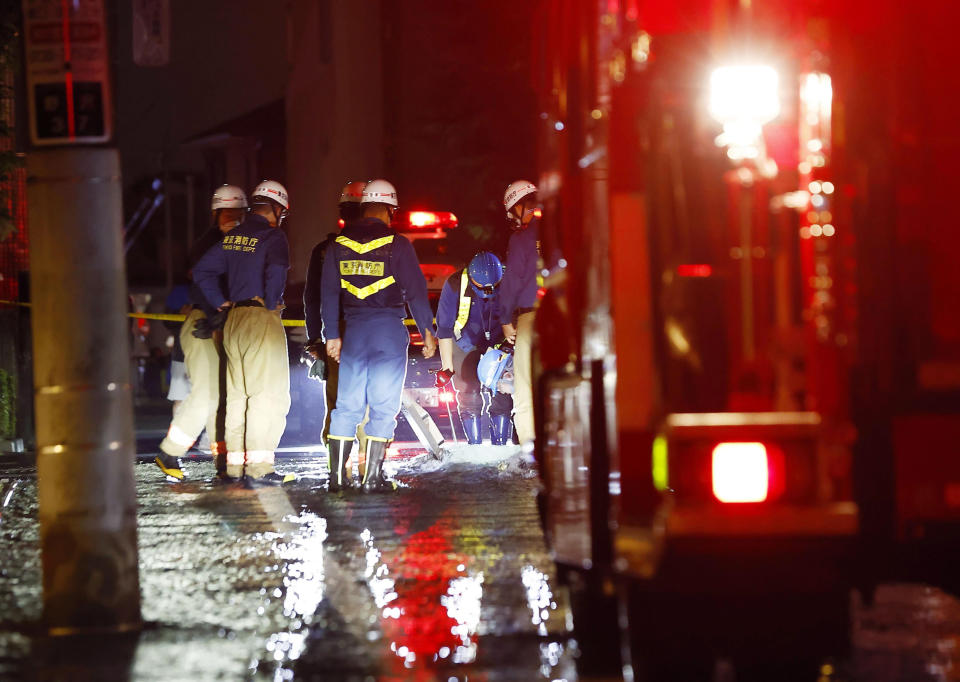 Firefighters work on an inundated road following an earthquake, in Tokyo, early Friday, Oct. 8, 2021. A powerful earthquake shook the Tokyo area on Thursday night, halting trains and subways. (Kyodo News via AP)