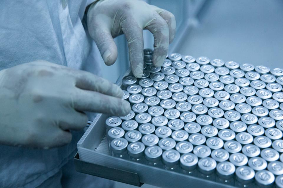 SAO PAULO, BRAZIL - APRIL 23: An employee holds a container with bottles of vaccines while working on the production line of CoronaVac, Sinovac Biontech's vaccine against COVID-19 at Butantan biomedical production center on April 23, 2021 in Sao Paulo, Brazil. While Butantan Institute works on developing its own vaccines, continues to produce the Chinese CoronoVac developed in partnership with the Chinese laboratory Sinovac Biontech. Brazil already announced that due to lack of vaccines, will finish inoculating high risks groups by September and not by May as it had been announced. The Butantan Institute requested authorization to the Sanitary Surveillance Agency (ANVISA) to start clinical tests with Butanvac, a new vaccine against COVID-19 100% developed in Brazil. (Photo by Alexandre Schneider/Getty Images)