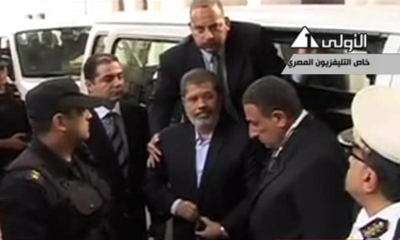 """This image made from video broadcast on Egyptian State Television shows ousted President Mohammed Morsi arriving for a court hearing at a police academy compound in Cairo, Egypt, Monday, Nov. 4, 2013. After four months in secret detention, Egypt's deposed Islamist president defiantly rejected a court's authority to try him Monday, saying he was the country's """"legitimate"""" leader and those that overthrew him should face charges instead. The trial was then adjourned until Jan. 8 after several interruptions.(AP Photo/Egyptian State Television via AP video)"""