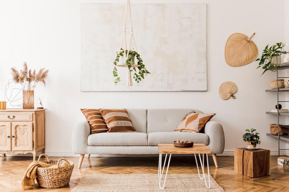 The stylish boho interior of open room in cozy apartment withdesign furnitures and elegant personal accessories. Template. Home decor. Honey yellow concept.