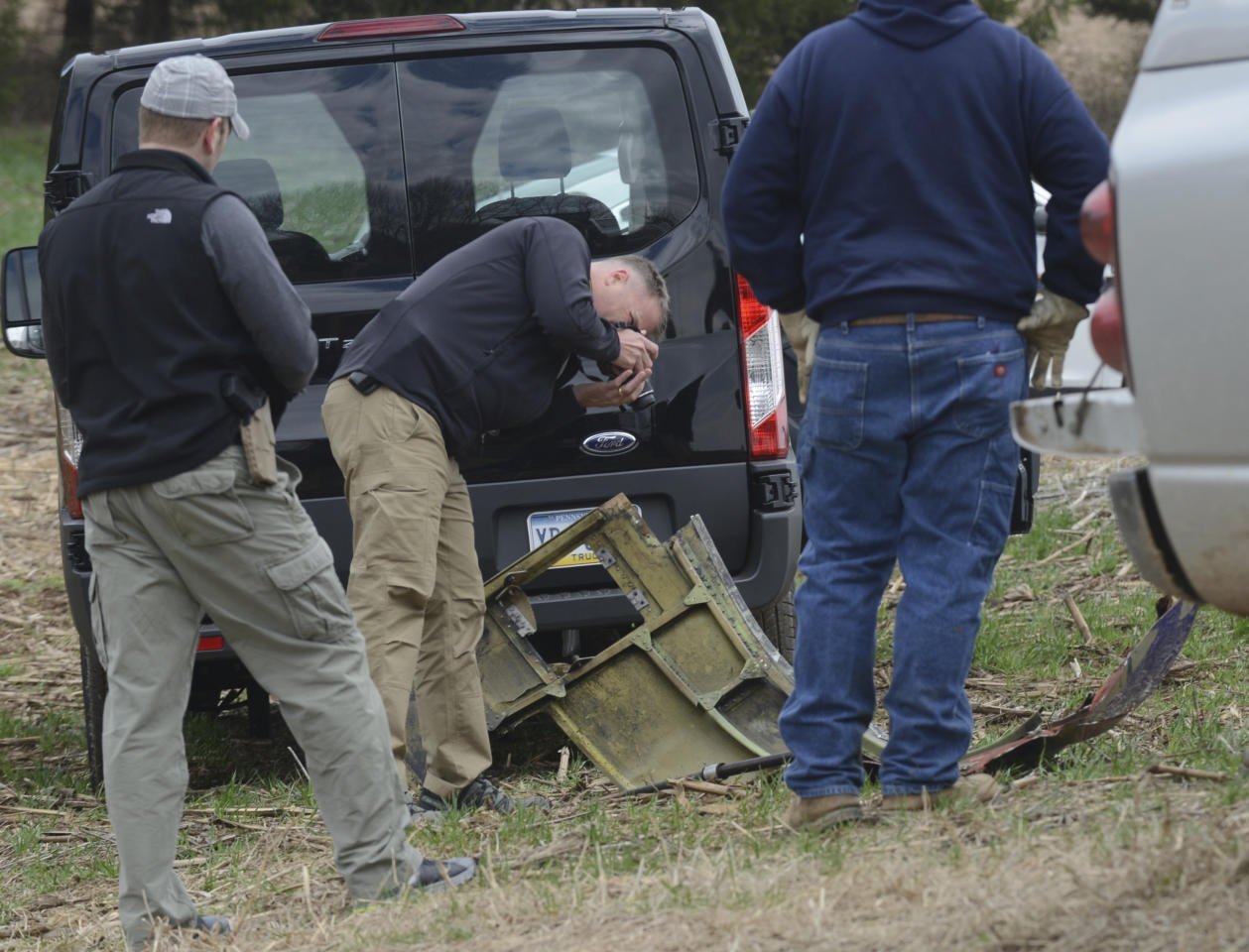 <p>A National Transportation Safety Board investigator photographs a piece of debris that landed in Penn Township, Berks County field from a plane that made an emergency landing Tuesday after a fatal engine mishap, Wednesday, April 18, 2018, on state game lands. (Photo: Bill Uhrich/Reading Eagle via AP) </p>