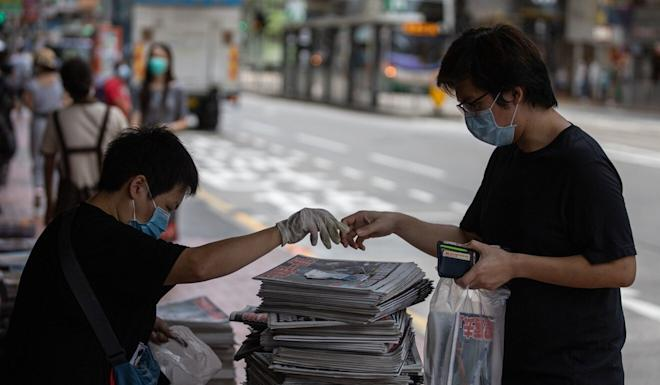 A man buys a copy of Apple Daily the day after founder Jimmy Lai was arrested under the new national security law. Photo: EPA-EFE