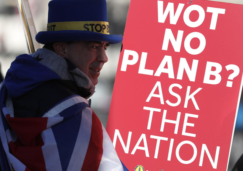 Anti Brexit protester Steve Bray who is almost permanently demonstrating outside the Houses of Parliament watches the traffic as he holds up placards in London, Monday, Jan. 28, 2019. British Prime Minister Theresa May faces another bruising week in Parliament as lawmakers plan to challenge her minority Conservative government for control of Brexit policy. (AP Photo/Alastair Grant)