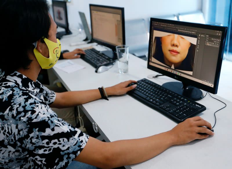 A printing shop employee editing customer's photo designs a face mask, amid the coronavirus disease (COVID-19) outbreak, in Jakarta