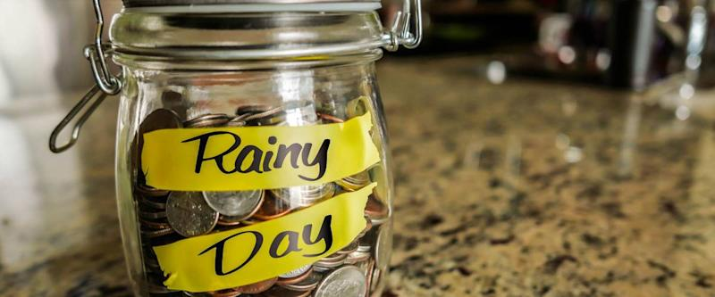 clear glass filled with coins that says rainy day denoting an emergency fund