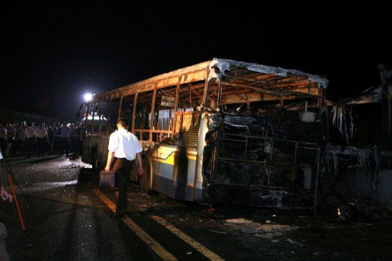 Investigators are seen at the scene where a bus caught fire in Xiamen, China, on June 7, 2013