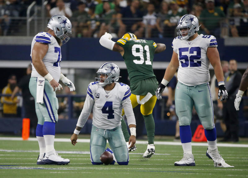 Dallas Cowboys' Travis Frederick, left, and Connor Williams (52) watch Dak Prescott (4) get up off the ground after being sacked by Green Bay Packers' Preston Smith (91) during the first half of an NFL football game in Arlington, Texas, Sunday, Oct. 6, 2019. (AP Photo/Ron Jenkins)