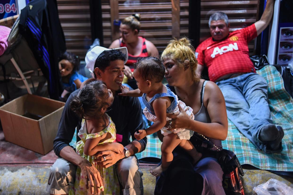 A Honduran migrant family taking part in a caravan heading to the US, rest on their arrival to Huixtla, Chiapas state, Mexico, on 22 October 2018: JOHAN ORDONEZ/AFP/Getty Images