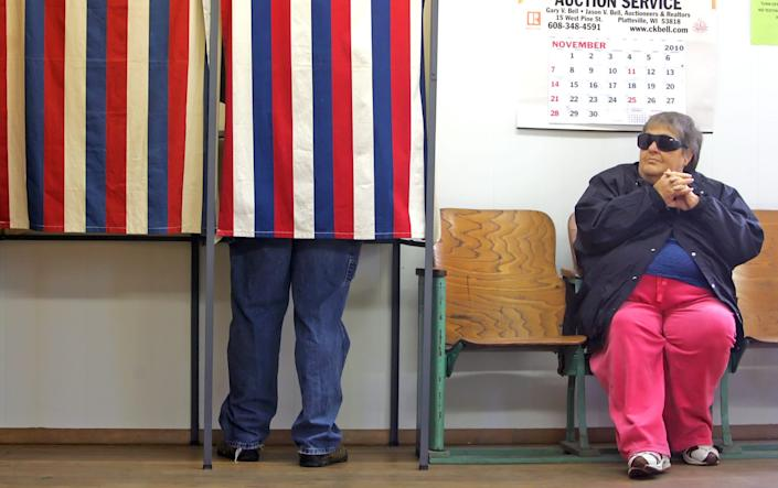 Jo Ann Banfield, of Cuba City, Wisc., waits as her son Ryan casts a vote on her behalf at the townhall in Georgetown, Wisc., on Nov. 2, 2010. Banfield is blind and is allowed to have someone vote on her behalf, according to poll workers.
