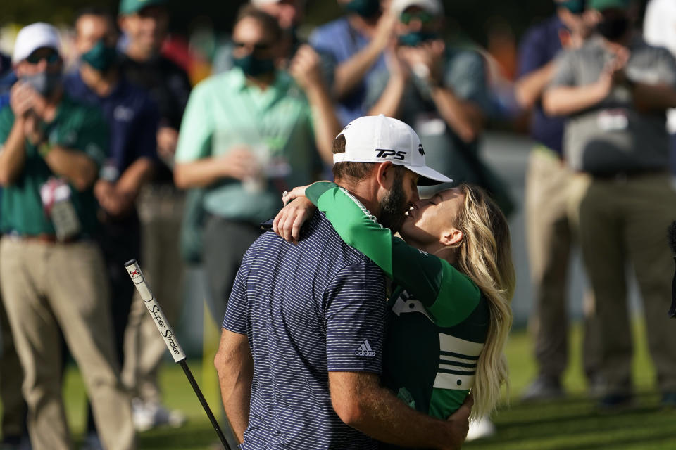 Dustin Johnson is hugged by Paulina Gretzky after winning the Masters golf tournament Sunday, Nov. 15, 2020, in Augusta, Ga. (AP Photo/David J. Phillip)