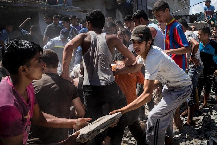 Palestinian men gather remove the rubble of a house hit by an airstrike in the al-Shati refugee camp in Gaza City on August 4, 2014 (AFP Photo/Marco Longari)