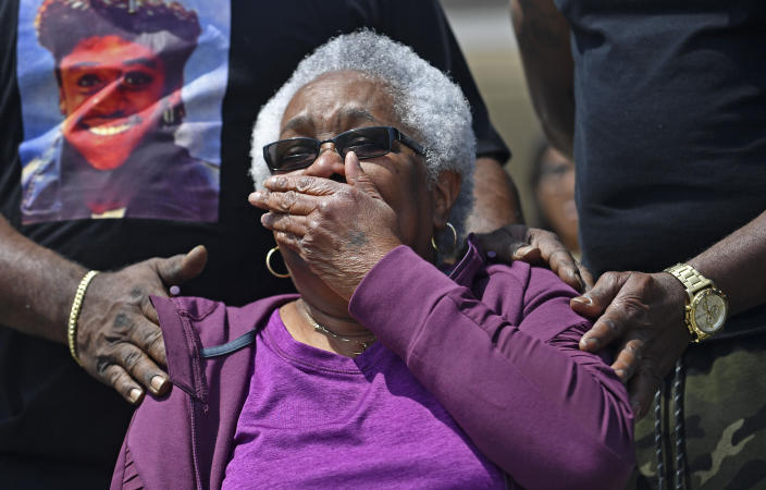 """Jessie Hamilton, seated, reacts as she is presented with a check to pay off her mortgage as LSU FIJI graduates gather to surprise their former house kitchen staff member, Saturday, April 3, 2021, and celebrate """"Jessie Hamilton Day"""" in Baker, La. (Hilary Scheinuk/The Advocate via AP)"""