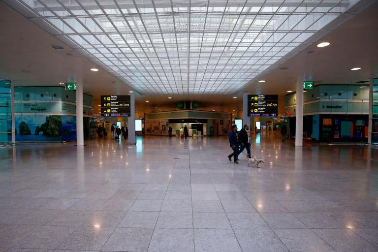Two people walk a dog at a virtually deserted Terminal 1 of Barcelona's El Prat -- while in Madrid, barking is one of few sounds breaking the silence in the capital's desrted streets