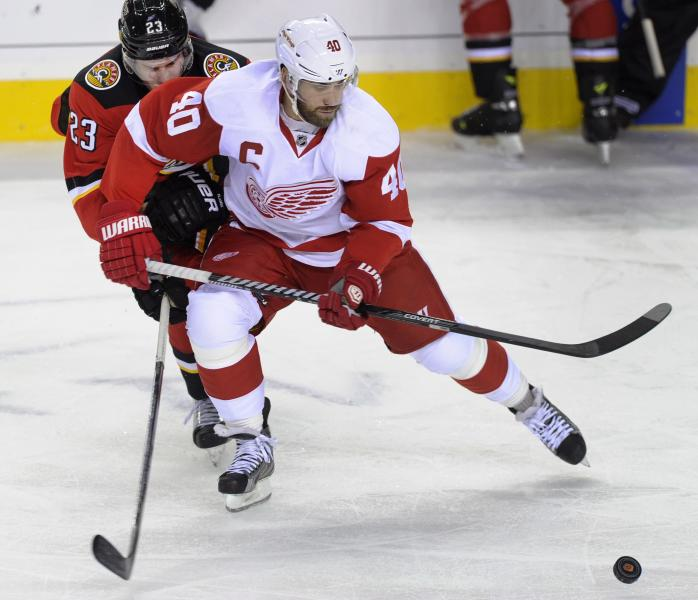 Detroit Red Wings' Henrik Zetterberg, right, from Sweden, vies for the puck with Calgary Flames' Sean Monahan during the second period of an NHL hockey game Friday, Nov. 1, 2013, in Calgary, Alberta. (AP Photo/The Canadian Press, Larry MacDougal)