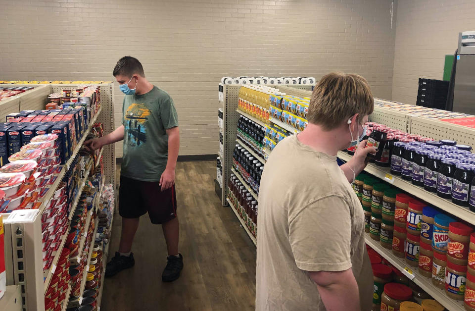 In this photo provided by Anthony Love, student Hunter Weertman, 16, left, stocks shelves and takes inventory while working as a manager of the student-led free grocery store at Linda Tutt High School on Nov. 20, 2020, in Sanger, Texas. The store provides food, toiletries and household items to students, faculty and community members in need. (Anthony Love via AP)