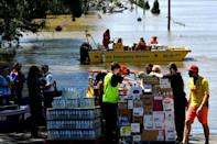 Members of the State Emergency Service transport relief goods during rescue operations at a flooded residential suburb of Sydney