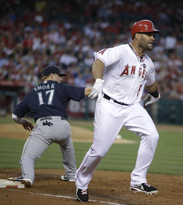 Los Angeles Angels' Albert Pujols, right, reacts after he was forced out by Seattle Mariners first baseman Justin Smoak during the third inning of a baseball game in Anaheim, Calif., Tuesday, June 18, 2013. (AP Photo/Jae C. Hong)
