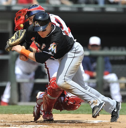 Miami Marlins' Chris Coghlan, foreground, is tagged out at home plate by Chicago White Sox catcher Hector Gimenez after a single by Justin Ruggiano during the second inning of a baseball game in Chicago, Sunday, May 26, 2013. (AP Photo/Paul Beaty)