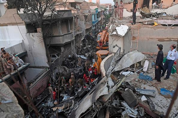 Security personnel search for victims in the wreckage of a Pakistan International Airlines aircraft after it crashed in a residential area in Karachi.