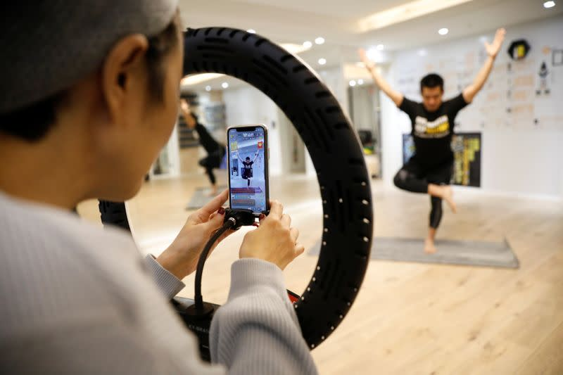 Liu Xiaojin, adjusts a phone during trainer Wang Kai's livestreamed gym class, as the country is hit by an outbreak of the new coronavirus, in Beijing