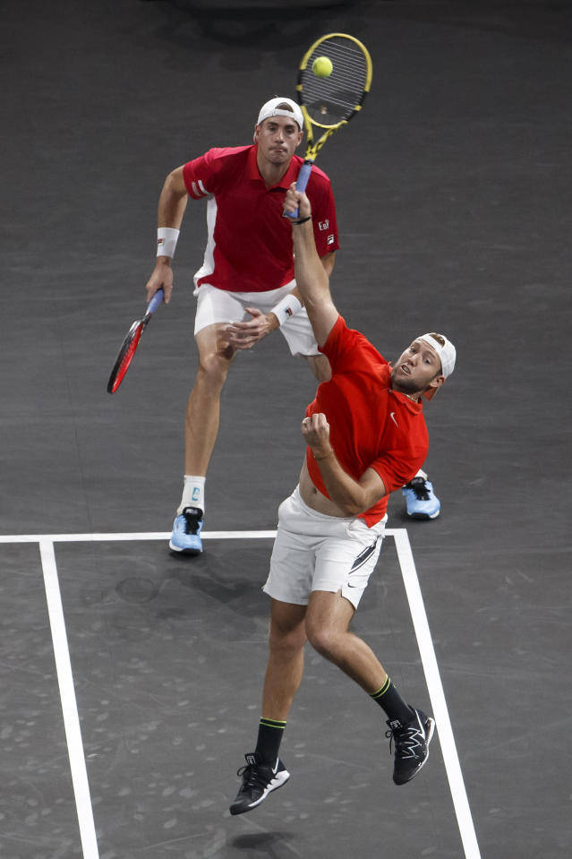 Team World's John Isner, rear, and teammate Jack Sock, front, play against Team Europe's Stefanos Tsitsipas and Roger Federer during a men's doubles tennis match at the Laver Cup tennis event in Geneva, Sunday, Sept. 22, 2019. (Salvatore Di Nolfi/Keystone via AP)