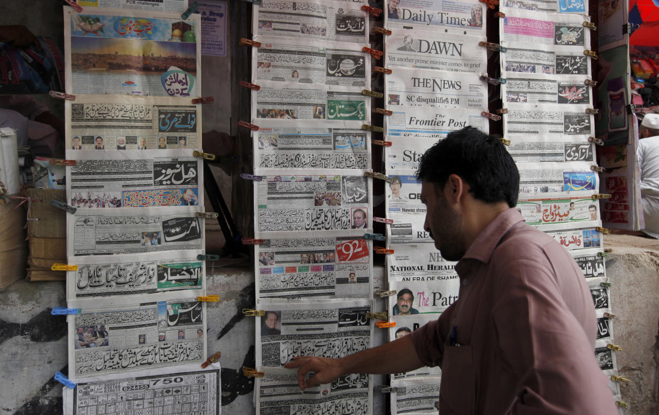 A man reads the morning newspaper displaying the front-page story of the disqualification of Prime Minister Nawaz Sharif by Supreme Court at a stall in Islamabad, Pakistan, Saturday, July 29, 2017. A top leader from the ruling party of deposed Prime Minister Sharif says a meeting of the party's lawmakers has been convened to consider who will be the country's next premier. (AP Photo/Anjum Naveed)