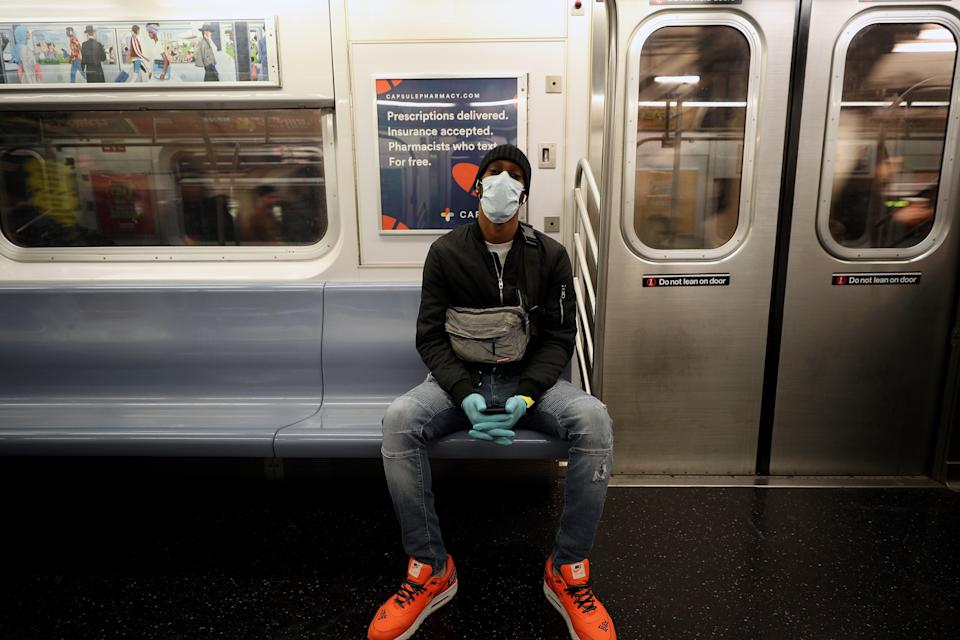 NEW YORK, USA - MARCH 11: A man wears a face mask and surgical gloves to prevent Covid-19 spread, at the New York City subway train in New York, United States on March 11, 2020. (Photo by Tayfun Coskun/Anadolu Agency via Getty Images)
