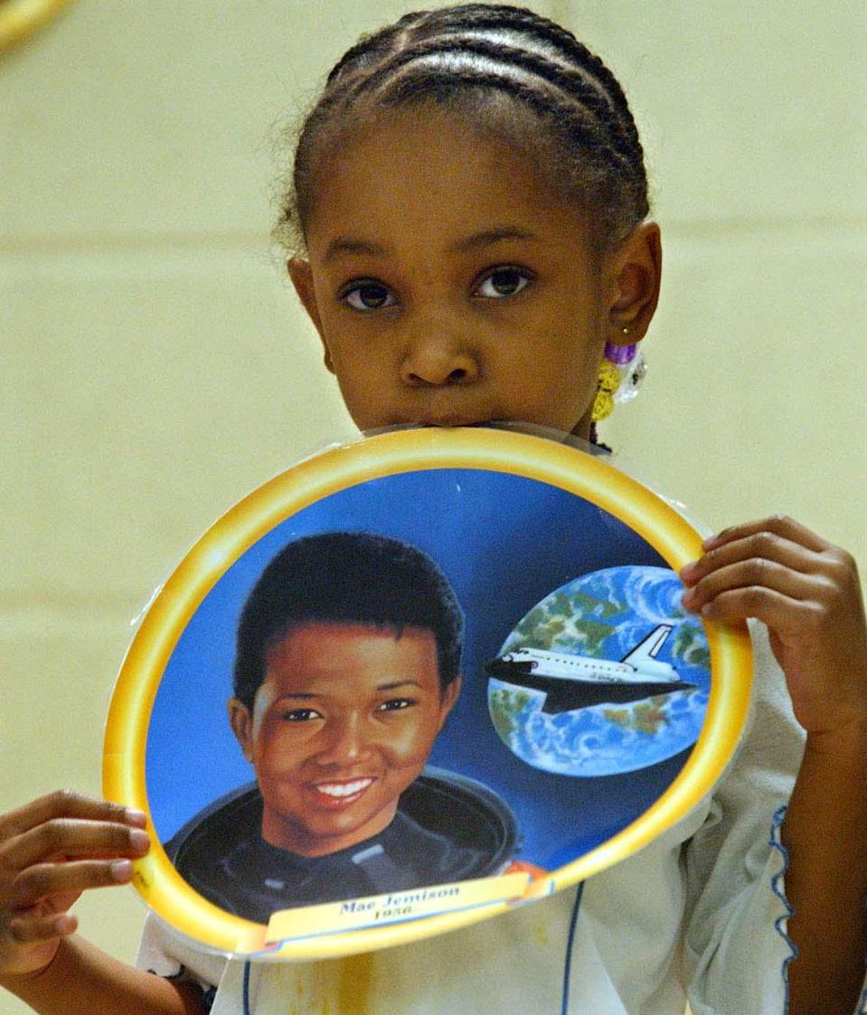 Culver Elementary School first grade student Infiniti Collins holds a picture of Mae Jemison, the first female African-American astronaut during an African American History Month. (Photo: AP Photo/ Evansville Courier & Press/Bob Gwaltney)