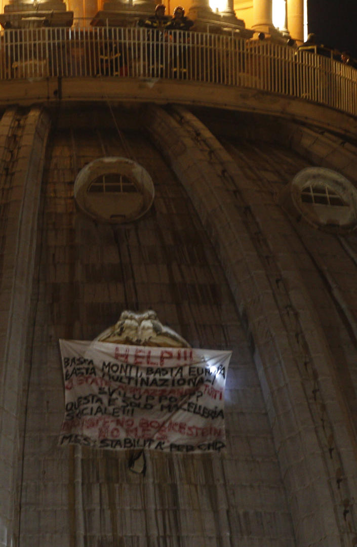 Italian firefighters, top, look at a banner hanging from a window of St. Peter's dome at the Vatican, Tuesday, Oct. 2, 2012. (AP Photo/Alessandra Tarantino)