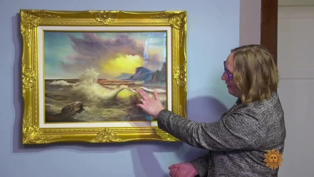 Curator Jessica Jenkins points out a Bob Ross seascape. / Credit: CBS News