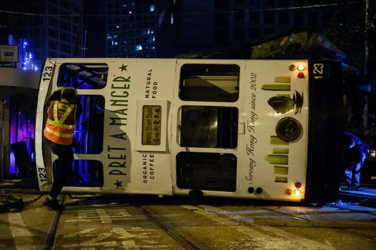 Five women and nine men were injured when a Hong Kong tram flipped over in the city's financial district in the early hours of Thursday