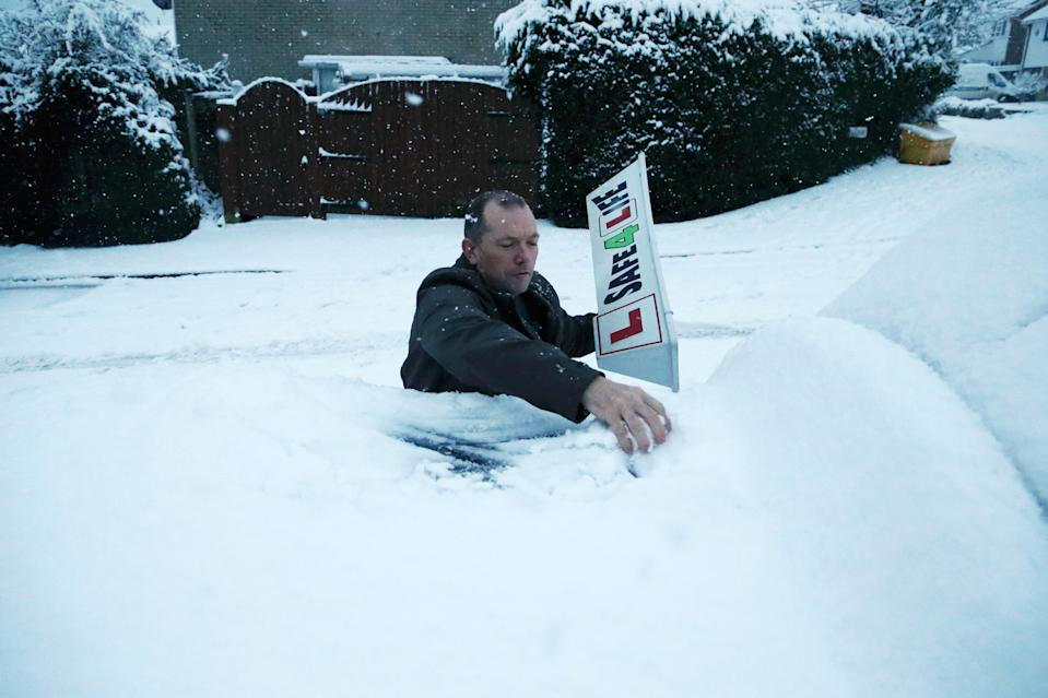 STOURBRIDGE, ENGLAND - DECEMBER 28: Driving instructor Steve Smith removes snow off the top of his car as heavy snowfall falls down on the west midlands overnight on December 28, 2020 in Stourbridge, England. (Photo by Cameron Smith/Getty Images)