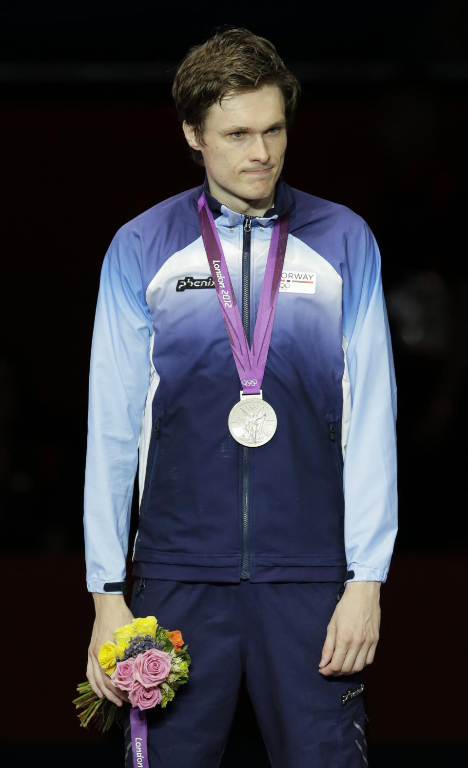 Norway's Bartosz Piasecki stands on the victory stand after winning the silver medal in men's individual epee fencing competition at the 2012 Summer Olympics, Wednesday, Aug. 1, 2012, in London.(AP Photo/Dmitry Lovetsky)