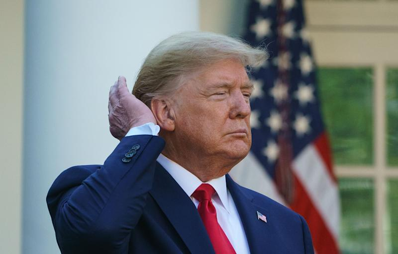 President Donald Trump pats down his hair as he speaks during the Coronavirus Task Force daily briefing on COVID-19 in the Rose Garden. (MANDEL NGAN via Getty Images)