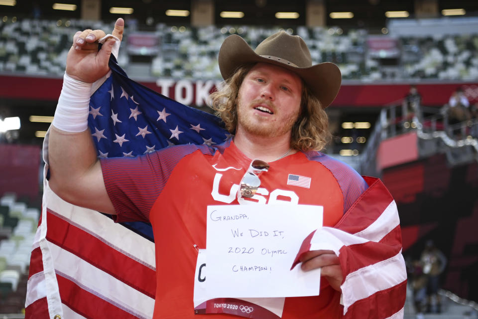 Ryan Crouser, of United States, holds a sign while celebrating winning the gold medal in the final of the men's shot put at the 2020 Summer Olympics, Thursday, Aug. 5, 2021, in Tokyo, Japan. (Matthias Hangst/Pool Photo via AP)