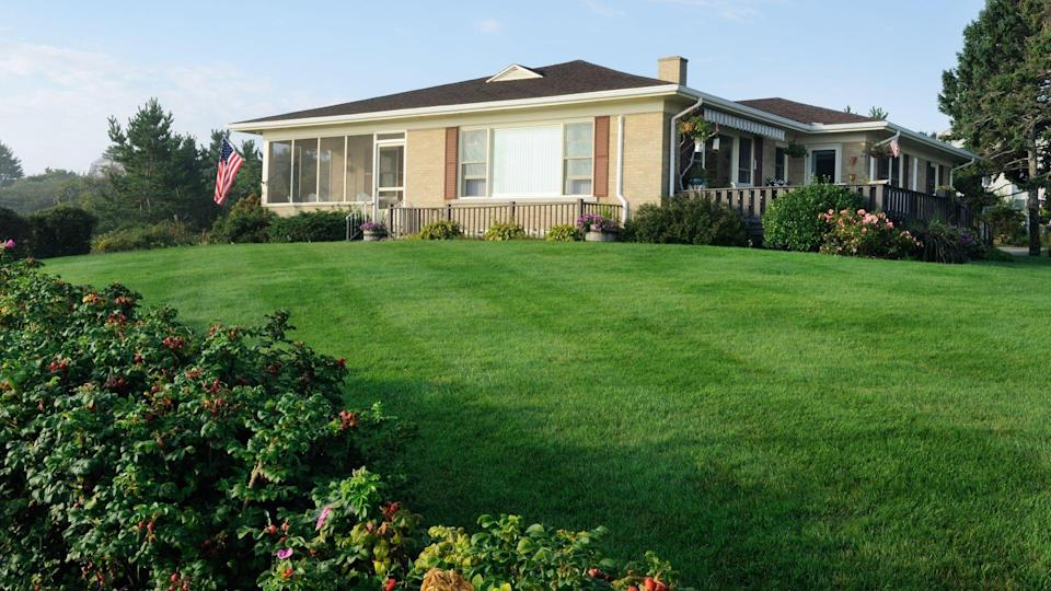 Classic american bungalow from the 60's or 70's with freshly cut lawn.