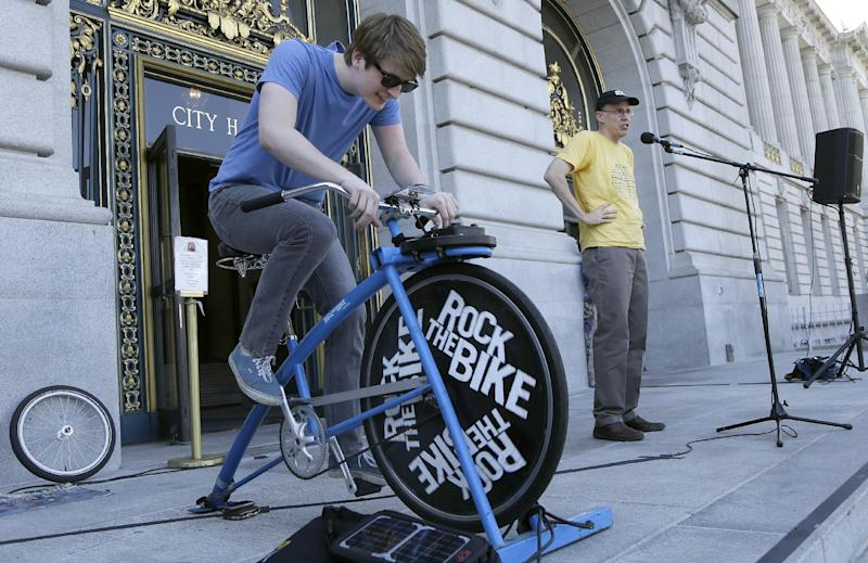 "Bill McKibben, founder of 350.org, right, speaks to a crowd of college students and supporters at a rally to support fossil fuel divestment outside of City Hall in San Francisco, Thursday, May 2, 2013. Hayden Higgins, left, rides a Rock The Bike ""One Bike/One Speaker,"" a bicycle that generated power for the sound system at the rally. (AP Photo/Jeff Chiu)"
