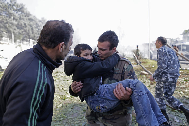 A Lebanese soldier carries an injured boy away from the site of a car bomb explosion in the suburb of Beir Hassan, Beirut, Lebanon, Wednesday, Feb. 19, 2014. The bombing in a Shiite district in southern Beirut killed several people on Wednesday, security officials said — the latest apparent attack linked to the civil war in neighboring Syria that has killed and wounded scores of people over the last few months. (AP Photo/Hassan Ammar)