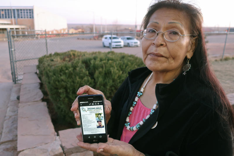 """In this Jan. 14, 2020, photo, Margaret Bitsue displays a flier that features her son who she reported missing more than two years ago, Tuba City, Ariz. Bitsue hasn't seen or heard from Brandon Sandoval, the youngest of her four children, in more than two years. """"I spend most of my days looking down the road expecting him to come up,"""" Bitsue says. The woman's words are soft but capture a room at a Navajo Nation government center, where people are gathered to talk not about women and girls who have disappeared or been killed, but men.  (AP Photo/Felicia Fonseca)"""