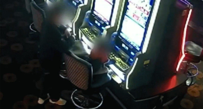A man stands back and watches as the toddler presses buttons on the gaming machine.