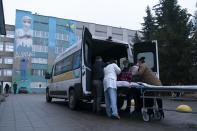 Medical workers transfer a coronavirus patient from an ambulance to a hospital organized in the medical college in Lviv, Western Ukraine, on Monday, Jan. 4, 2021. A medical college in western Ukraine has been transformed into a temporary hospital as the coronavirus inundates the Eastern European country. The foyer of the college in the city of Lviv holds 50 beds for COVID-19 patients, and 300 more were placed in lecture halls and auditoriums to accommodate the overflow of people seeking care at a packed emergency hospital nearby. (AP Photo/Evgeniy Maloletka)