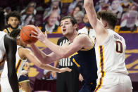 Michigan's Hunter Dickinson (1) drives as Minnesota's Liam Robbins (0) defends in the second half of an NCAA college basketball game, Saturday, Jan. 16, 2021, in Minneapolis. (AP Photo/Jim Mone)