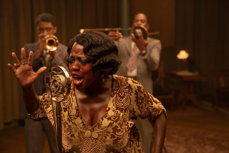 Ma Rainey (Viola Davis) singing into an old-fashion mic, with Levee (Chadwick Boseman) and Cutler (Colman Domingo) playing brass behind her
