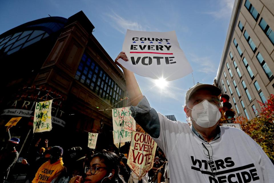 """People hold signs reading """"Count every vote"""" and """"Black votes matter."""""""
