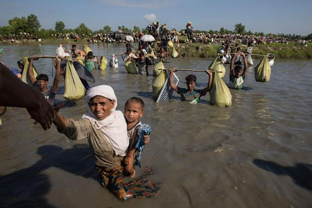 <p>Thousands of Rohingya refugees fleeing from Myanmar cross a small stream in the hot sun on a muddy rice field on October 16, 2017 near Palang Khali, Cox's Bazar, Bangladesh, on October 16, 2017. (Photograph by Paula Bronstein/Getty Images) </p>