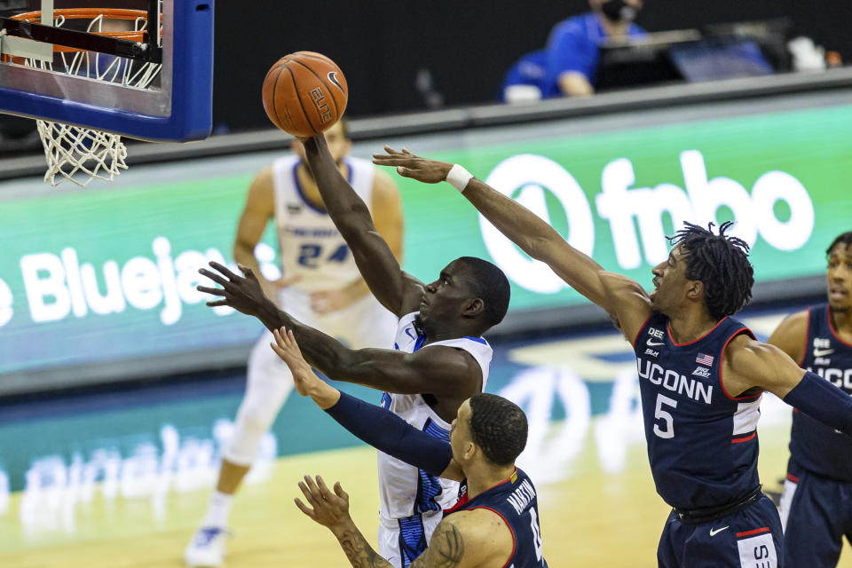 Creighton forward Damien Jefferson (23) makes a layup against Connecticut forward Isaiah Whaley (5) and guard Tyrese Martin (4) in the first half during an NCAA college basketball game Saturday, Jan. 23, 2021, in Omaha, Neb. (AP Photo/John Peterson)