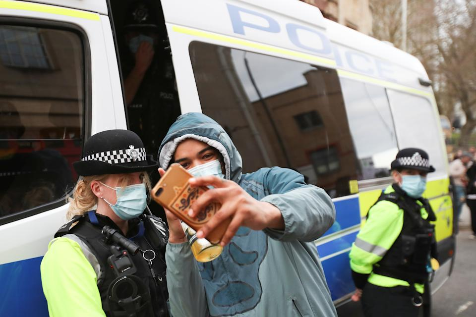 A demonstrator takes a selfie with a police officer as he takes part in a protest against a new proposed policing bill, in Bristol, Britain, March 21, 2021. REUTERS/Peter Cziborra