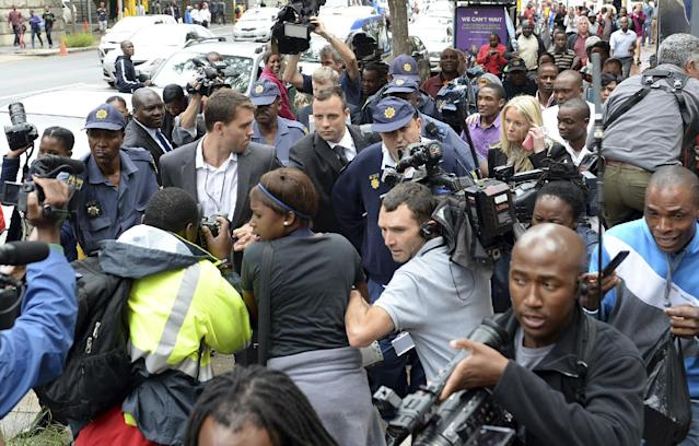 Oscar Pistorius, back center, is mobbed by media as he is escorted by police outside court during a recess on the third day of his trial at the high court in Pretoria, South Africa, Wednesday, March 5, 2014, Pistorius is charged with murder for the shooting death of his girlfriend, Reeva Steenkamp, on Valentines Day in 2013. (AP Photo/Antoine de Ras) SOUTH AFRICA OUT