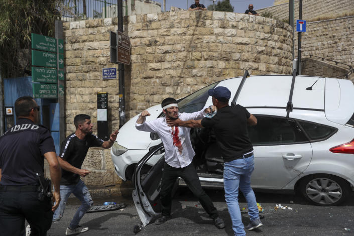 A Jewish driver, center, scuffles with Palestinians after he was attacked by Palestinian protesters near Jerusalem's Old City. Monday, May 10, 2021. Israeli police clashed with Palestinian protesters at a flashpoint Jerusalem holy site on Monday, the latest in a series of confrontations that is pushing the contested city to the brink of eruption. Palestinian medics said at least 200 Palestinians were hurt in the violence at the Al-Aqsa Mosque compound, including 150 who were hospitalized. (AP Photo/Ohad Zwigenberg)